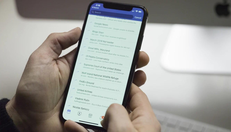 Человек держит телефон в руках с открытым приложением Facebook Messanger. Мы объясняем, как удалять сообщения в Facebook Messenger.