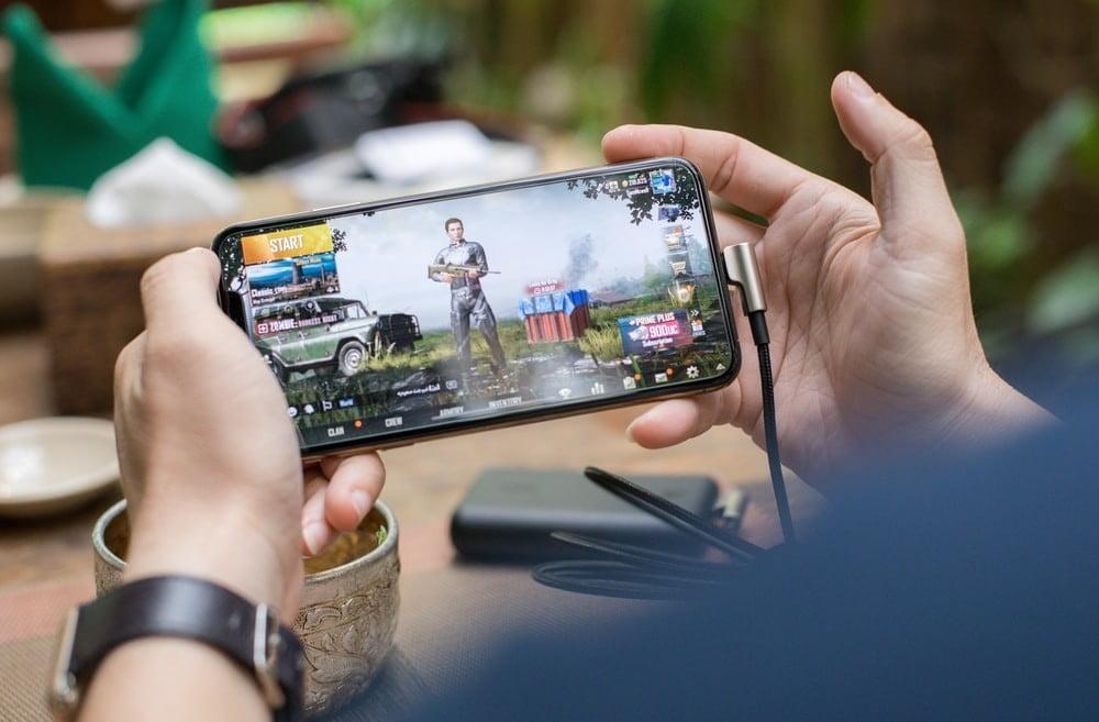 Человек играет на своем iPhone