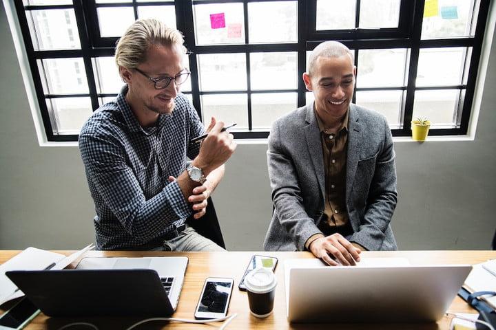 Двое мужчин улыбаются, глядя на экран компьютера Apple в офисе. Мы представляем самые веселые вопросы для Сири.