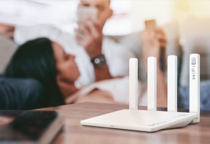 крупным планом Honor Router 3 сидит на столе в гостиной с молодой парой с помощью мобильного телефона