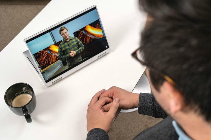 Мужчина смотрит видео на своем планшете 2-в-1 на столе и отводит чашку кофе