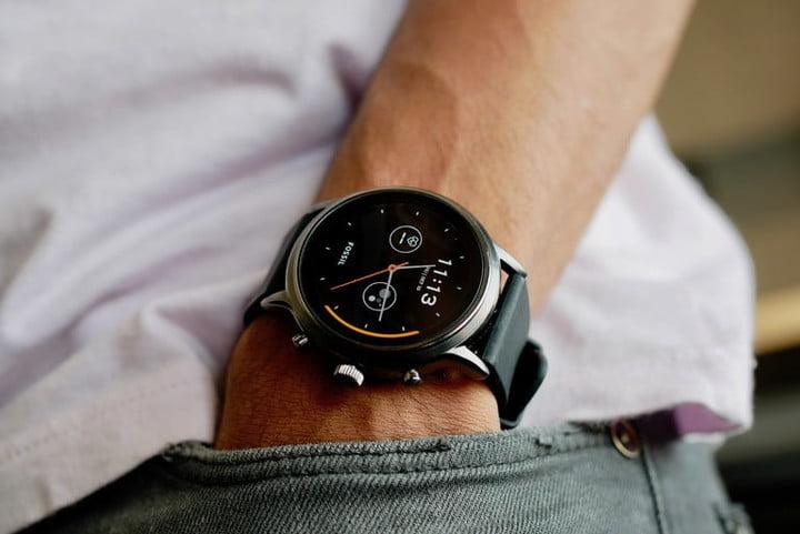 Человек держит руку в кармане и использует умные часы Fossil Gen 5 на своем лице