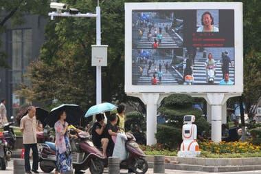 Оборудование для распознавания лиц и экран, предназначенный для смущения безрассудных пешеходов на оживленном перекрестке в Сянъяне 26 июня 2017 года